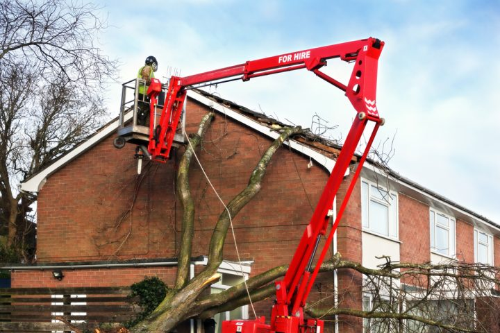 Tree surgeon removing fallen tree from roof of home using a cherry picker