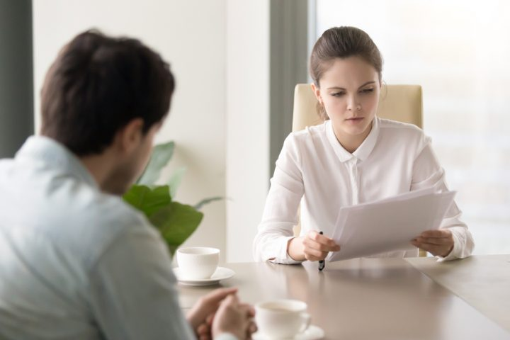 Young woman HR representative reviewing complaint with seriousness and concern